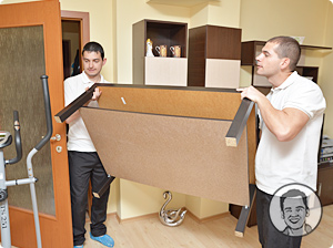 Two of Paul's Removalists Carrying a Coffee Table  Through the Door
